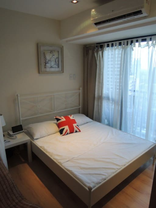 A queen-sized bed from Ikea, in front of the balcony which shows the amazing view of Makati City