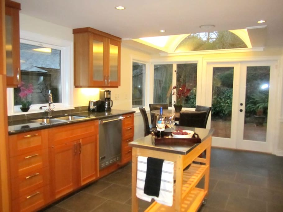 Deluxe gourmet kitchen with marble pub table and french doors open to large deck.