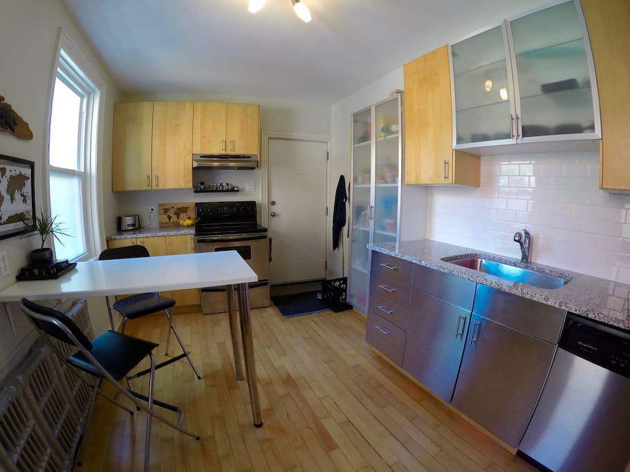 Kitchen with oven, toaster, microwave, dish washer, fridge and double sink. Includes back entrance from parking. Seating for 2 or 4 (additional seats not shown)