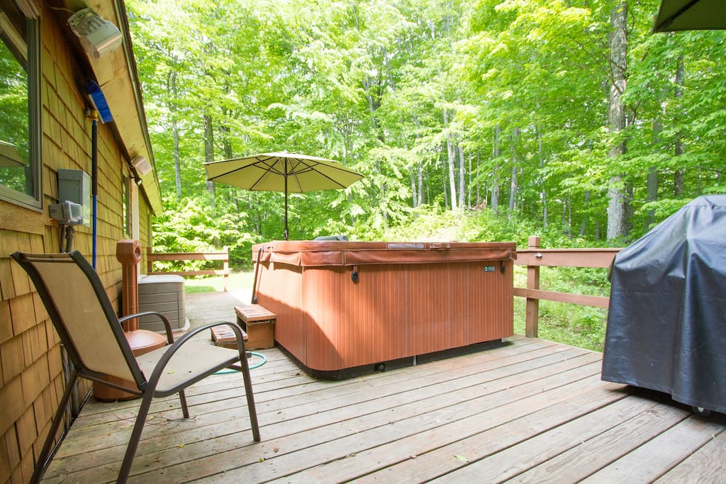 Back deck with two BBQ grills, hot tub, chairs and umbrellas