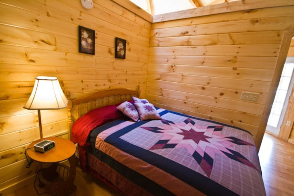 Queen bed in the Love Shack Yurt cabin at Country  Road Cabins in Hico, WV