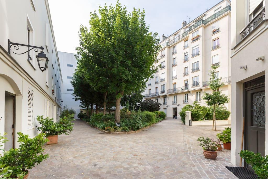 Jardin et vue sur la 2ème cour, l'appartement est dans le bâtiment au fond à droite.