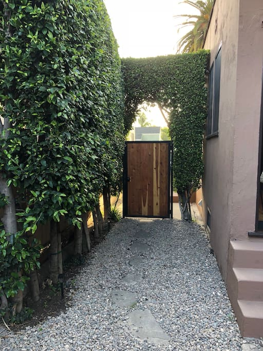 Beautiful hedge covered private entrance with craftsman wood style door and private gated entrance.