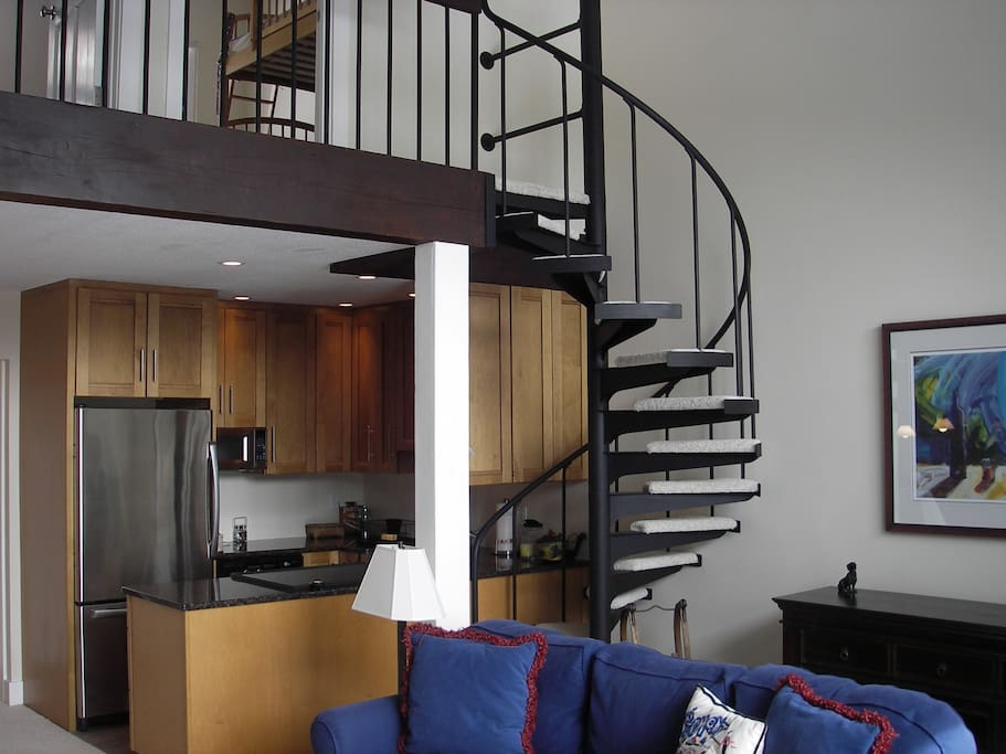 Open living area with open, spiral staircase. Please note - staircase is NOT childsafe!