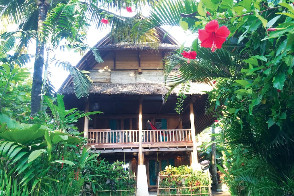 FAMILY SURF BUNGALOW (upstairs~above the Garden Triple Room ~Ideal for 6 persons)  •Bedroom 6x6m2  •3 queen size beds with mosquito nets  •Balcony 3x6m2, 2 hammocks and a table  •Bathroom 2x3m2, western standard toilet, hot and cold shower, sink and mirror  •Fan  •In-room safety box  •Writing desk  •TV local channels   •Breakfast for 6 persons
