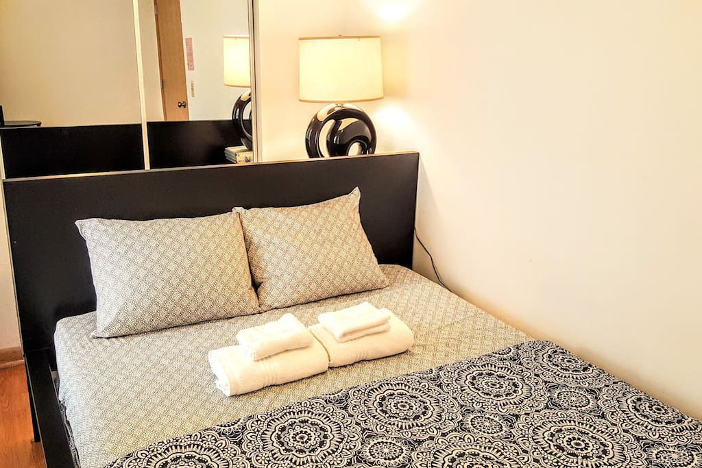 Queen-sized bed with clean linens and towels. This is exactly what your room will look like when you check-in.