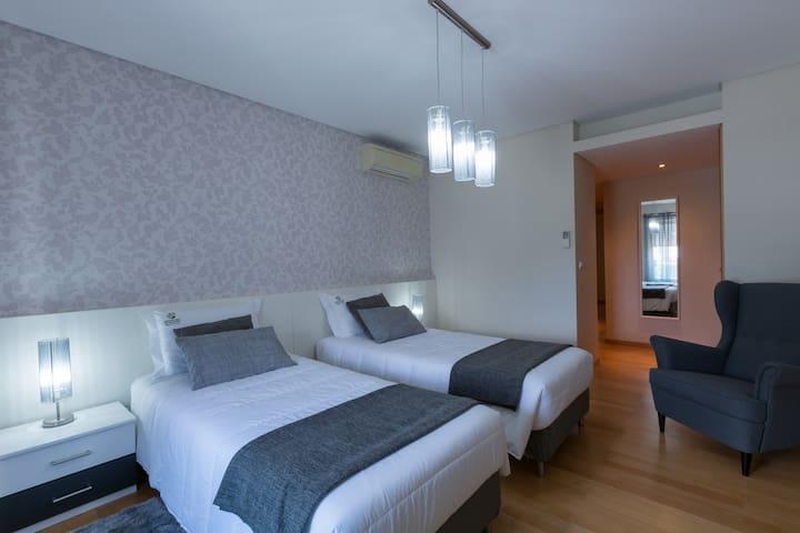 Quarto cinza com duas camas de solteiro