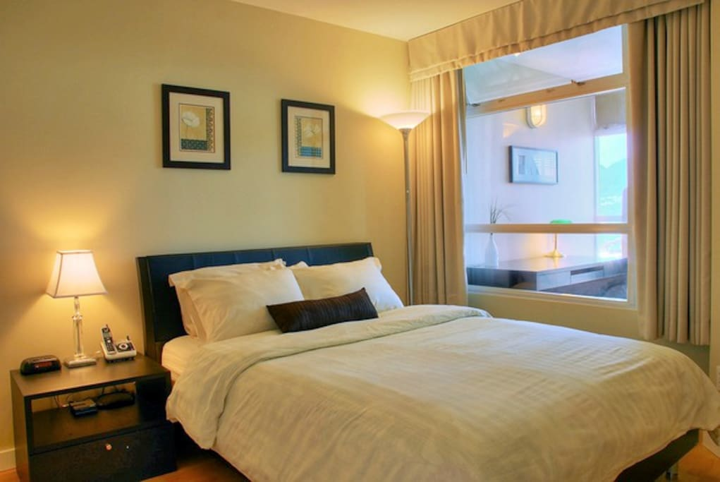 Master bedroom with queen bed, artwork and ample lighting