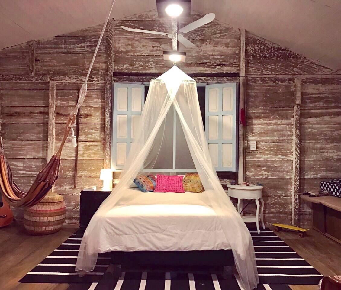 Romantic master bedroom at night. Both rooms have hammocks.