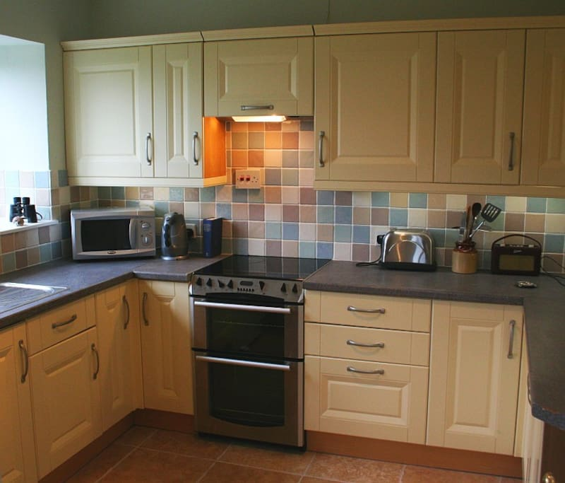 Fully fitted kitchen with views to the wild bird feeding area of the garden and valley