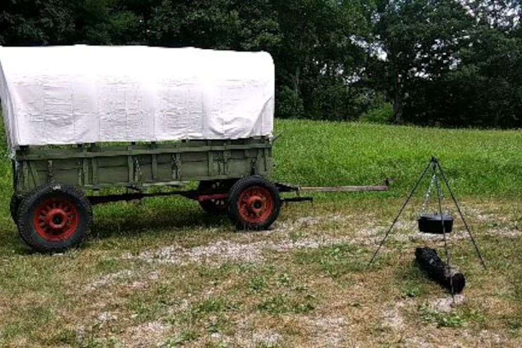 The good old wagon with new canvas top, sitting in front of the meadow where it will be moved when you arrive.