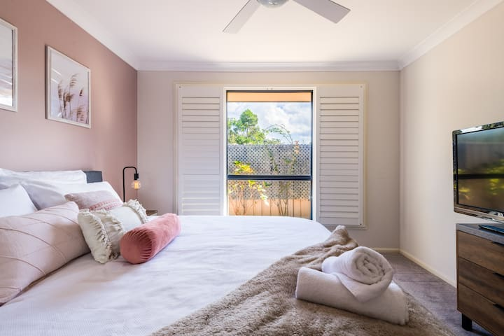 Master bedroom featuring King bed, ceiling fan, TV, built in robe and plantation shutters