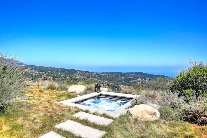 Enjoy a soak in a private hot tub, set before tumbling hillsides and the Pacific Ocean.