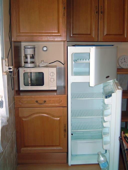 coin aménagé avec vaisselle, cafetière, bouilloire, micro-ondes, télé 36cm
