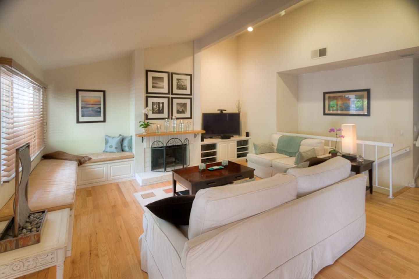 Bright living room with plenty of comfortable seating, TV, TiVo, DVD payer, and CD player.