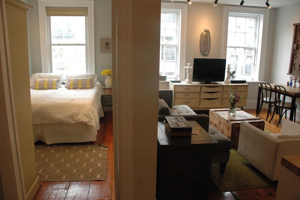 Sunny bedroom and living room, exposed brick, gorgeous floors, beautiful textiles and furniture.