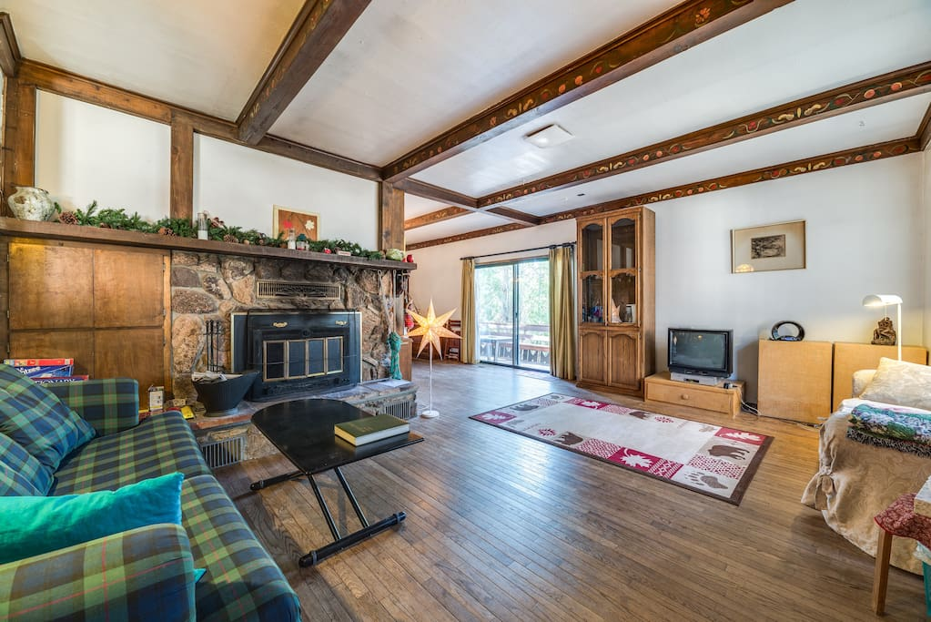 Spacious living room features solid-oak floors and a stone hearth.