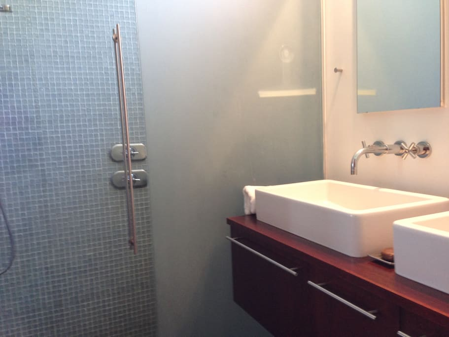 Glass tiled shower with two indivually controlled shower heads and plenty of fresh towels. Toilet and shower are only accessible from the bedroom (totally private).