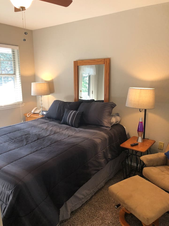 The Guest Rooms has a queen size bed, a little recliner, a landline telephone, alarm clock, side tables, a closet, a dresser, a large flat screen TV with Roku, DIRECTV NOW, Netflix, and other apps. This room has a door that opens to the lower deck of the home.