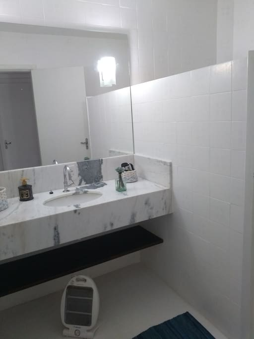 Banheiro dividido em três ambientes ,bancada de mármore com cuba embutida ,vaso sanitário e chuveiro.