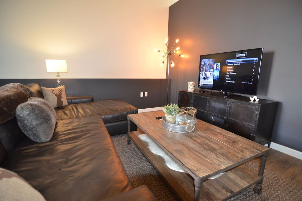 Inviting living room featuring deep leather sectional, flat screen TV w/ 200+ channels+ShowTime, and Apple TV (w/ HuluPlus + Netflix)