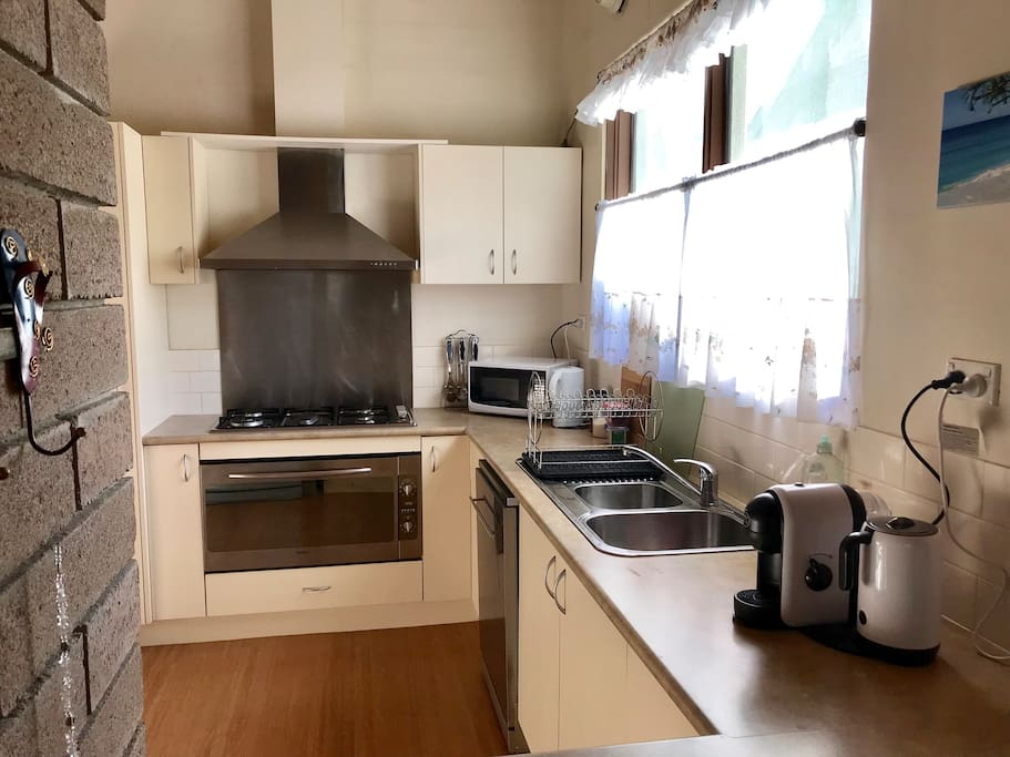 Fully equipped kitchen has Oven, fridge, microwave, dishwasher, coffee machine