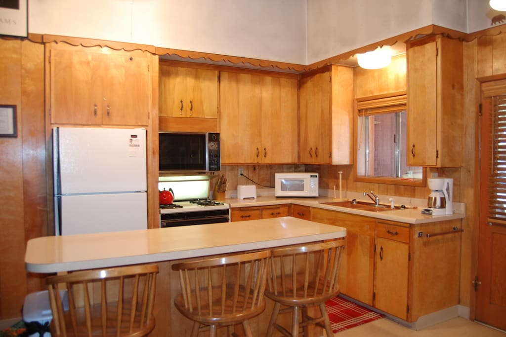 Kitchen with full size refrigerator, stove with oven, microwave and coffee maker