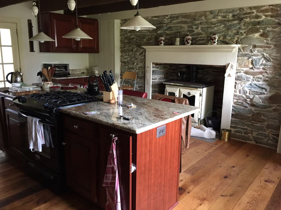 My newly renovated spacious kitchen with reclaimed red oak flooring, reused cherry kitchen cabinets, granite counter tops and my wood cookstove in the fireplace. Behind the island is the sink and fridge freezer.
