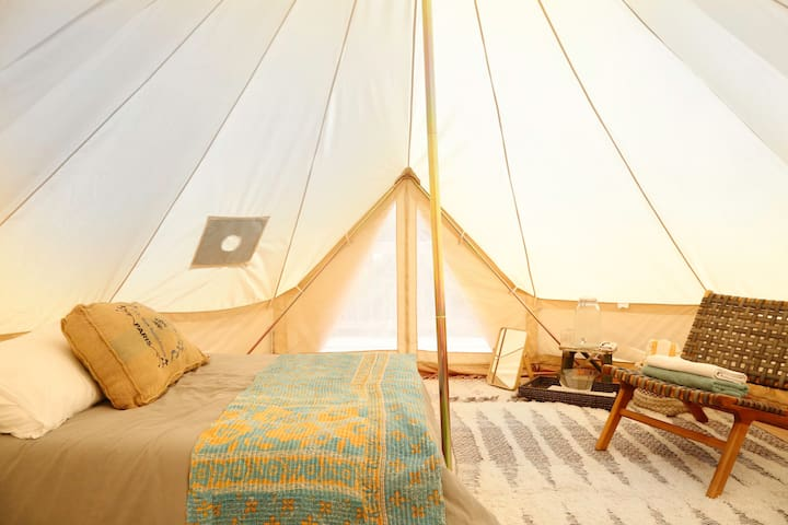 Upstate bell tent, one of 6 accommodations at Gatherwild, has a full size bed, with fresh linens, towels, and cozy textiles as well as a water basin for washing up.