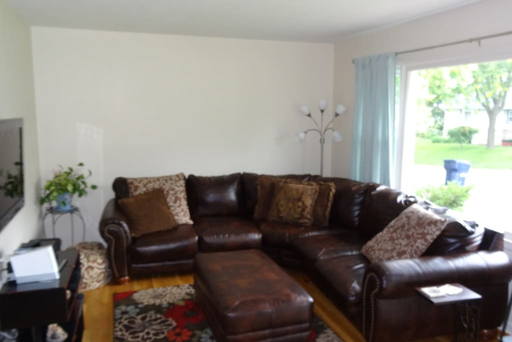 Living Room with large picture window, couch, ottoman, TV and DVD player.