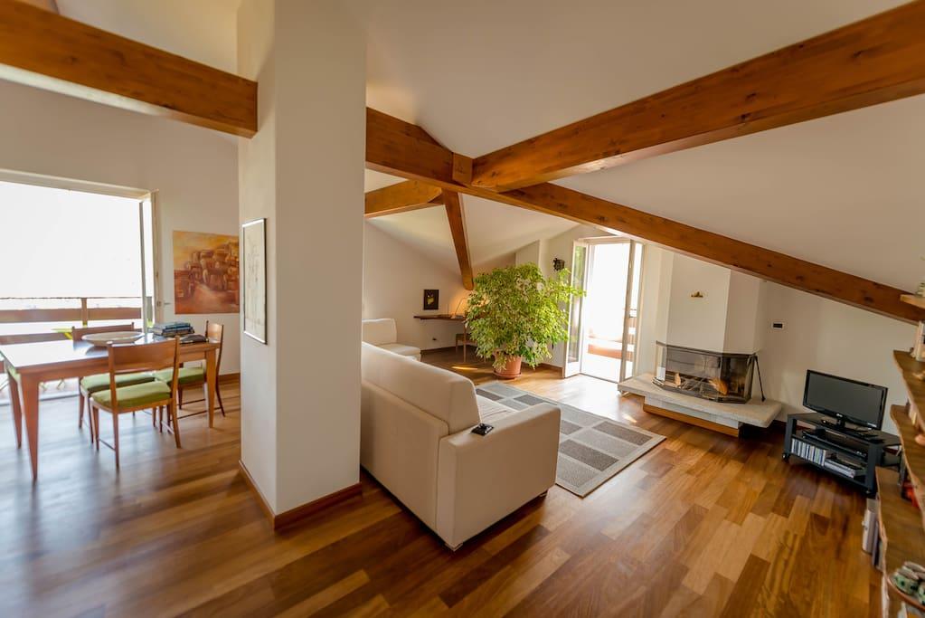 Zona pranzo/soggiorno con comodo divano letto matrimoniale, camino e balconi