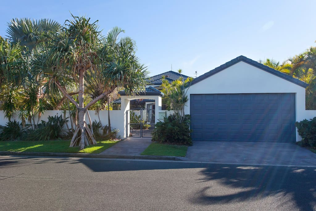 The street view of Sunbird with two large mature pandanus trees out the front. Off street parking or under cover in the carport area are available for guests.
