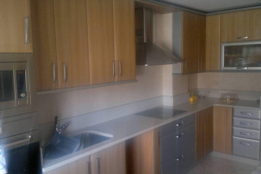 Cocina con electrodomésticos, nevera y utensilios básicos..
