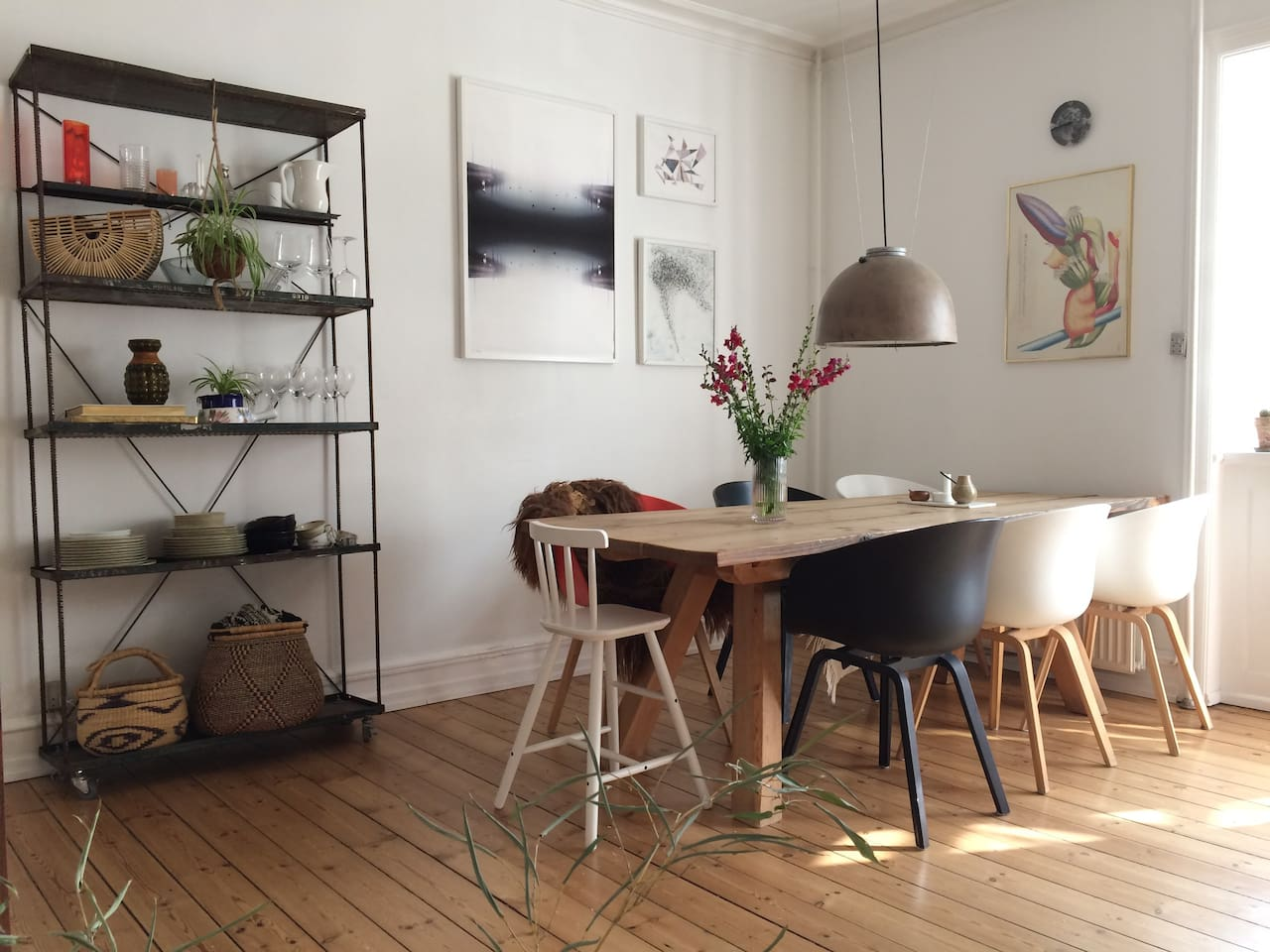 A handcrafted dining table with danish design HAY chairs and an original Copenhagen 'streetlight'