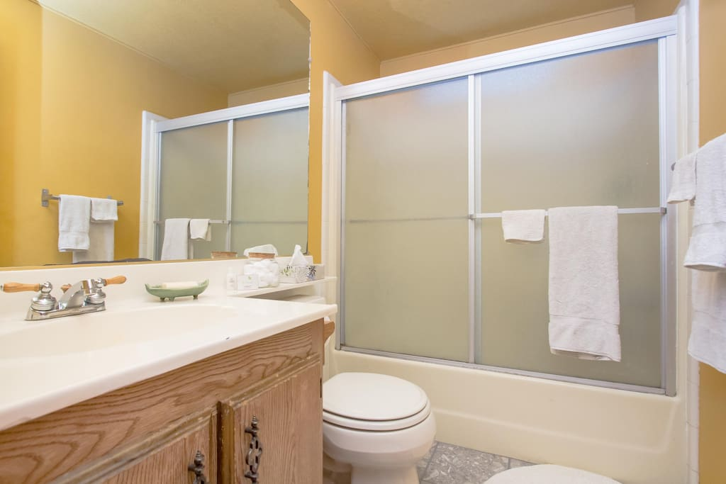 Bathroom adjacent to your bedroom has fresh towels and a handy, jumbo-sized mirror.