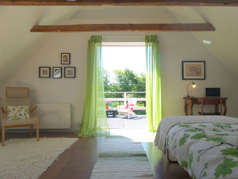 The green room looking out onto it's own wooden terrace with panoramic views.