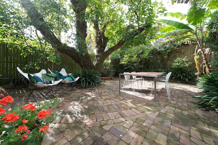 The towering white mulberry, garden and table with chairs