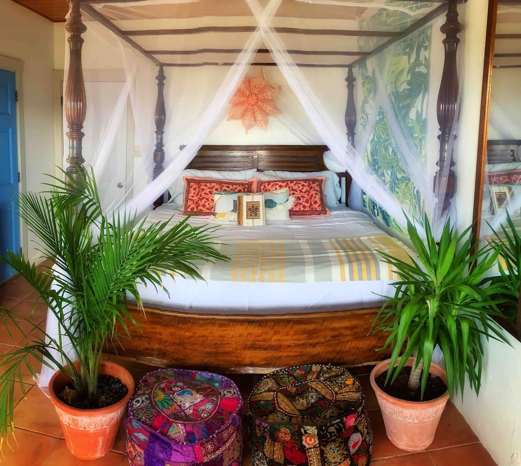 Bedroom #1: King-sized bed with mosquito netting; sitting area with coffee table, sliding glass doors with view out to St. Thomas, coffee bar and refrigerator, air conditioned