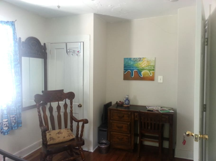 Mirror, desk and rocking chair in bedroom