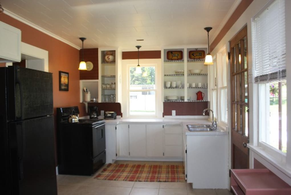 Large functional kitchen with lots of windows.