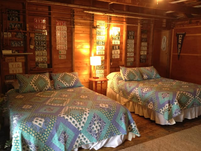 Two queen beds in one room of the two room cabin.