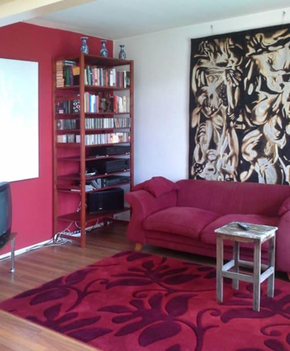 Zithoek in woon/eetkamer met tv, wifi, stereo met bluetooth,  boeken en bijzondere kunstobjecten.