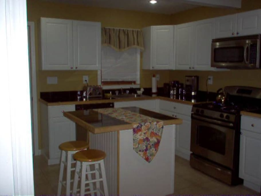 Kitchen has stainless steel appliances, ceramic tiled floor.