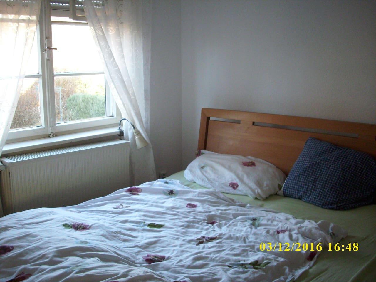 Schlafzimmer mit Blick in den Garten und direkten Zugang zu eigenem Badezimmer