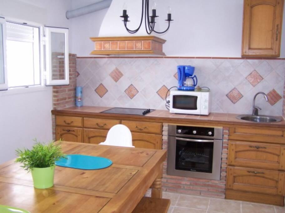 Cuisine entièrement équipée avec à côté son cellier et grande table à manger.