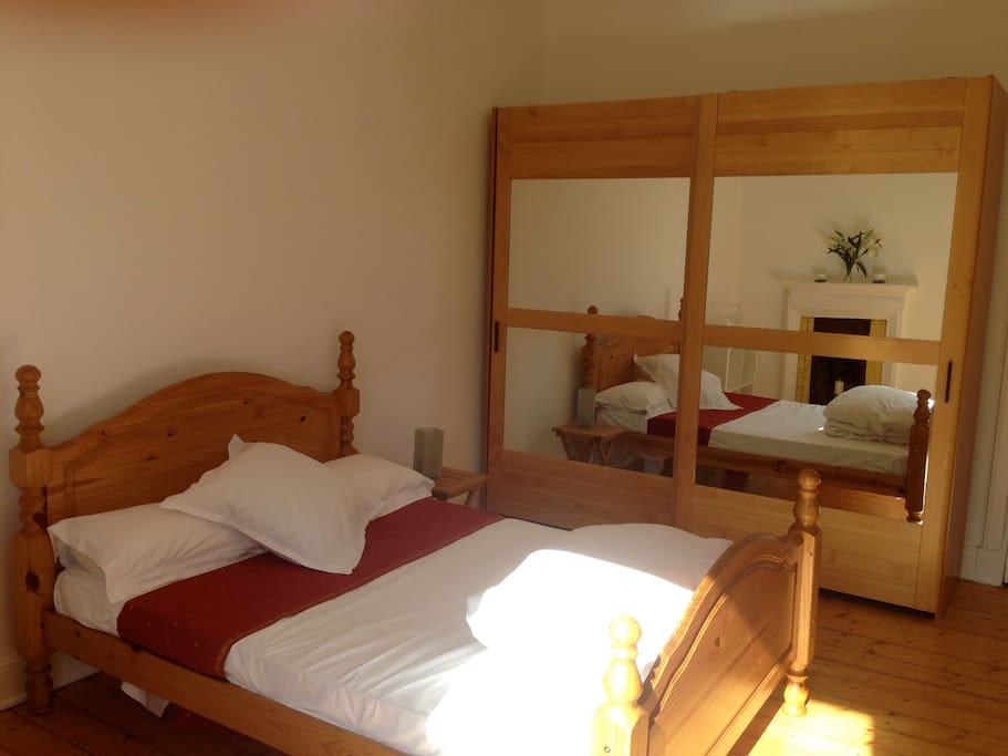 Sunlit double bed and large wardrobe.