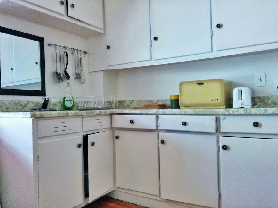 Entry-Level: the Kitchen has plenty of cabinet space, and you'll need the stool to reach most of it! Kitchen equipped with a toaster, water kettle, pots and pans, utensils, and with enough settings for up to eight people. West-facing window.