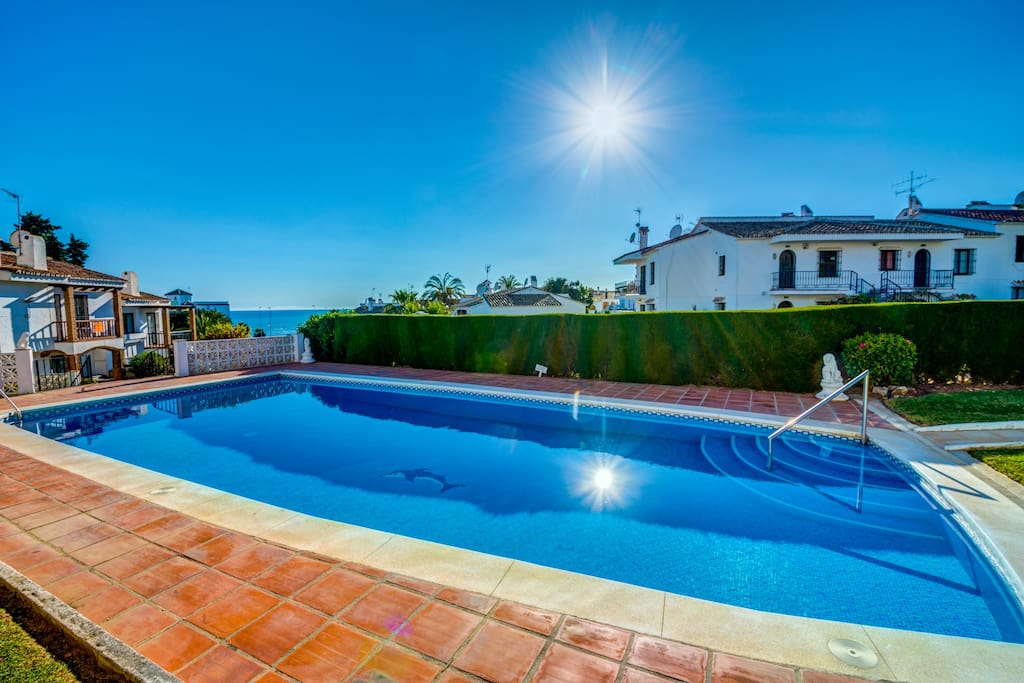 Lovely pool with sea views and with finely framed with garden and bushes.