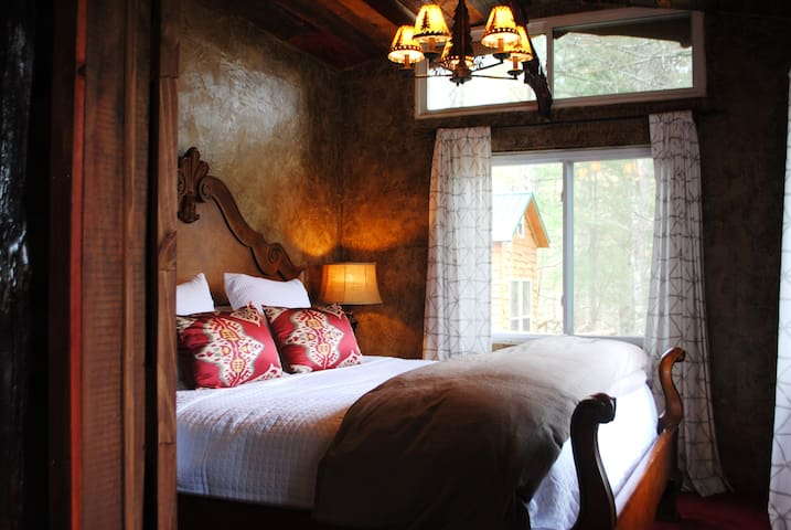 King sized bed in master bedroom on main level of cabin with vaulted barn wood ceilings.