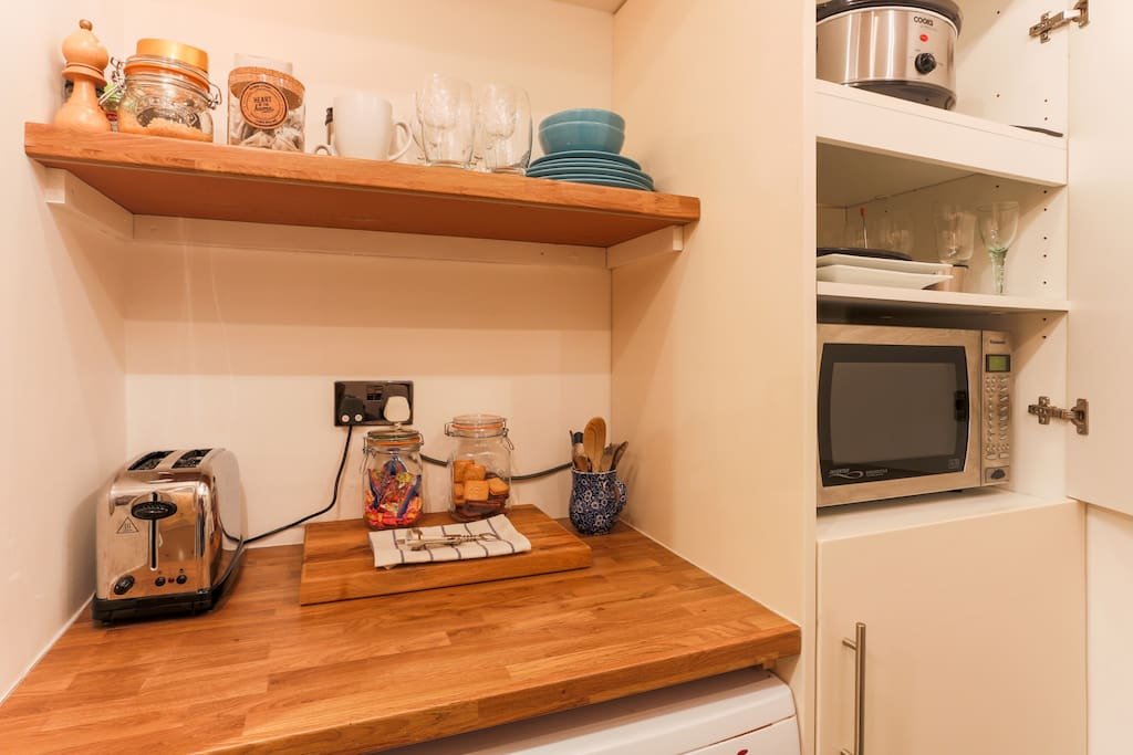 The kitchenette with microwave, slow cooker, toaster and kettle.